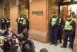 """St Pancras, London, January 16th 2016. Dozens of protesters hold an """"emergency demonstration and die-in"""" as France prepares to bulldoze the Jungle Camp at Calais. PICTURED: Police block the entrance to the Eurostar terminal as protesters stage a sit-in. ///FOR LICENCING CONTACT: paul@pauldaveycreative.co.uk TEL:+44 (0) 7966 016 296 or +44 (0) 20 8969 6875. ©2016 Paul R Davey. All rights reserved."""