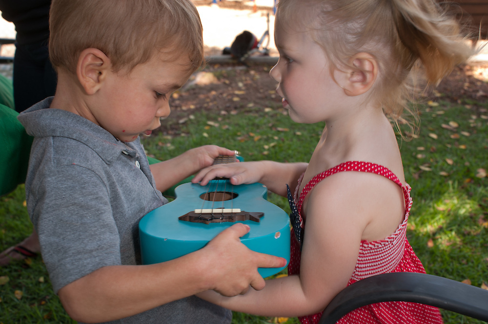 a three year old boy and girl exchange a glance while holding a ukulele