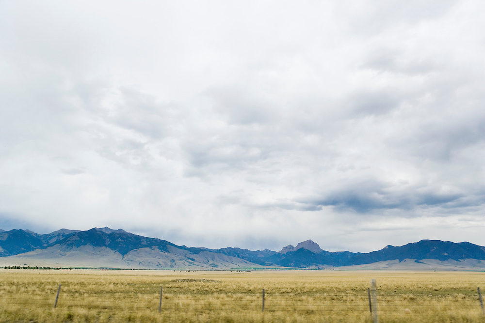Mountain, agricultural land, and sky as seen from highway 287 in Madison County, Montana, USA.