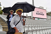 """Two spectators with umbrellas up in the stands as rain falls with the big screen showing a message """"We Are Summer"""" ahead of the International Test Match 2019 match between England and Australia at Lord's Cricket Ground, St John's Wood, United Kingdom on 14 August 2019."""