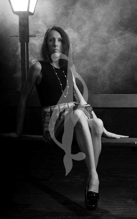 A model posing in a retro outfit on a bench.