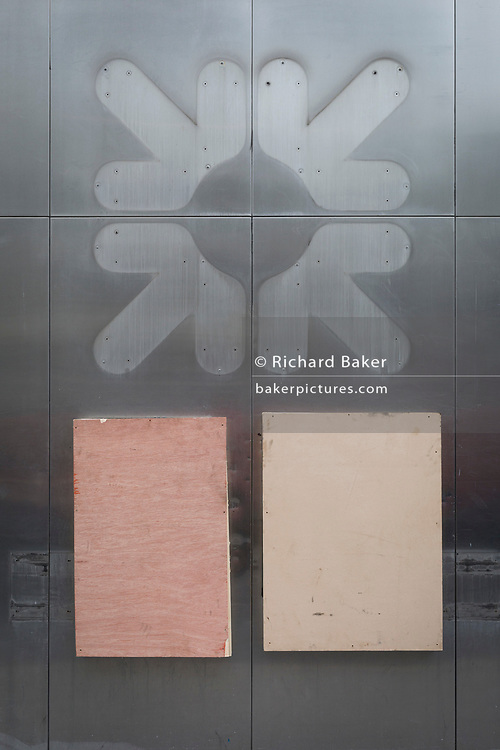 A detail of the exterior of a former RBS (Royal Bank of Scotland)bank where two cash dispensers (ATMs) are now removed, their apertures covered with plywood, and the company logo also gone to leave their traces on the wall on 4th February 2020, in the City of London, England. Royal Bank of Scotland was established in Edinburgh in 1727 and today employs almost 12,000 people and serves 1.8m personal customers and more than 110,000 business customers.