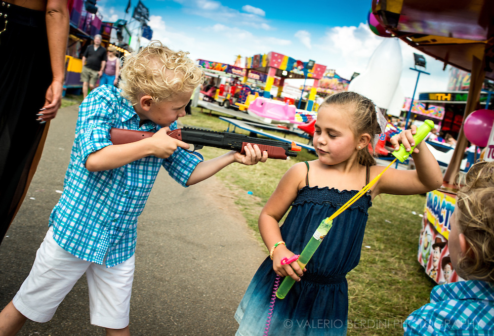 A boy with a toy rifle points at a girl with a bubble blower.