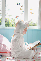 Young girl (5-6) sitting on bed in unicorn costume reading book side view