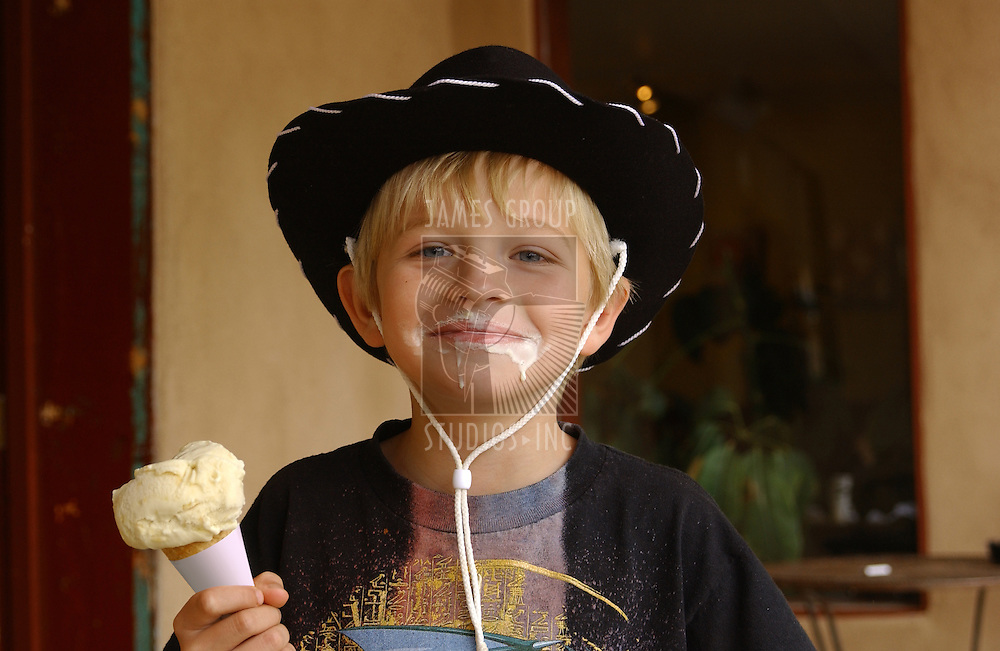 Young boy with cowboy hat eating an icecream cone
