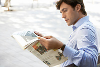 Mid-adult man reading newspaper on street