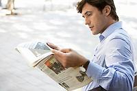 Mid-adult man reading newspaper on street
