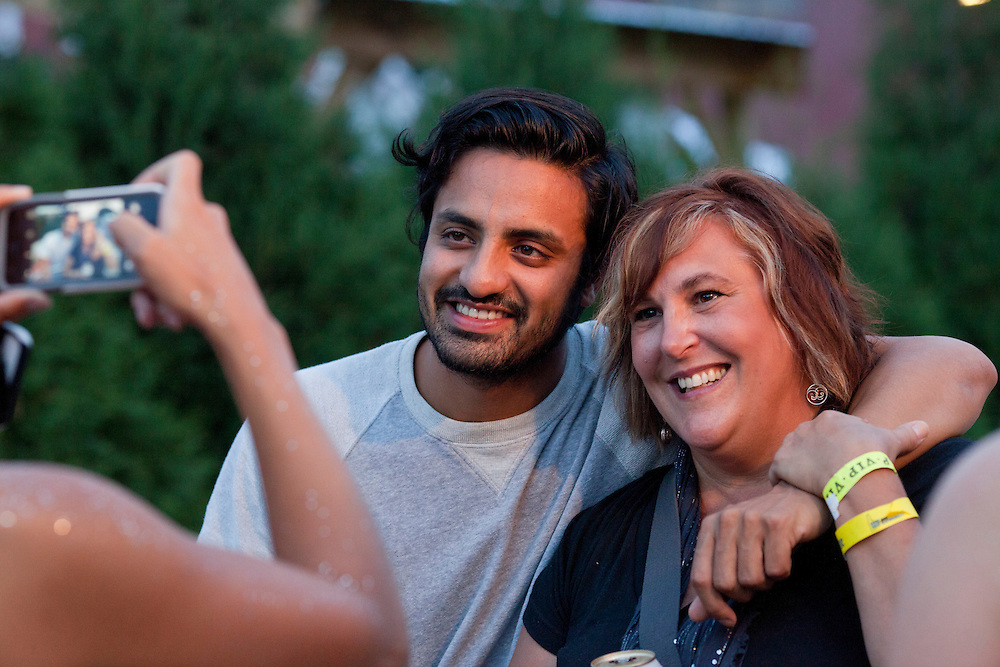 Sameer Gadhia of Young the Giant poses for a picture with Susan Anderson of North Liberty in the VIP area of the NewBo Music Fest in downtown Cedar Rapids on Saturday, August 8, 2015. (Rebecca F. Miller/Freelance for the Gazette)