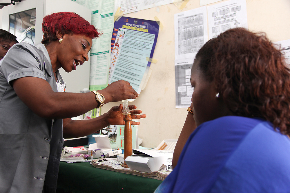 INDIVIDUAL(S) PHOTOGRAPHED: Bassey Immaculata (left) and Emem E (right). LOCATION: Epko Abasi Clinic, Calabar, Cross River, Nigeria. CAPTION: A family planning nurse provides information on how to correctly use a condom to prevent sexually transmitted diseases and protect against unwanted pregnancy.