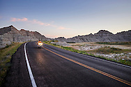 A motorcycle cruises the black paved highway in Badlands National Park, South Dakota at dusk.
