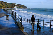 A man stands on the promenade looking out to sea with his two dogs near by on Sunny Sands Beach, Folkestone, Kent, UK. The tide is high covering all the beach and the sea is rough from stormy weather.  (photo by Andrew Aitchison / In pictures via Getty Images)