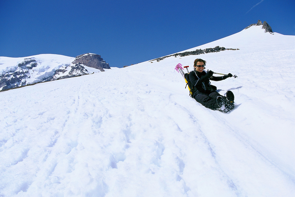 Woman sliding down Muir Snow Field Mt Rainier Washington USA&amp;#xA;<br />
