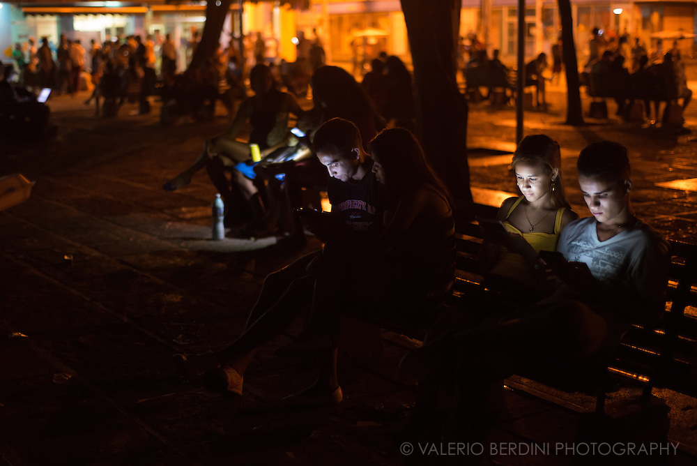 People lit up by her electronic devices in Parque Fe del Valle in Havana, Cuba, on the night of 28 December 2015. Since the arrive of wi-fi hotspots in Cuba, people gathers to videocall friends and relatives abroad, check e-mail, use social networks and explore the Internet. These people were awareof the photographer, but they continued using their devices. This photo was not staged.<br />