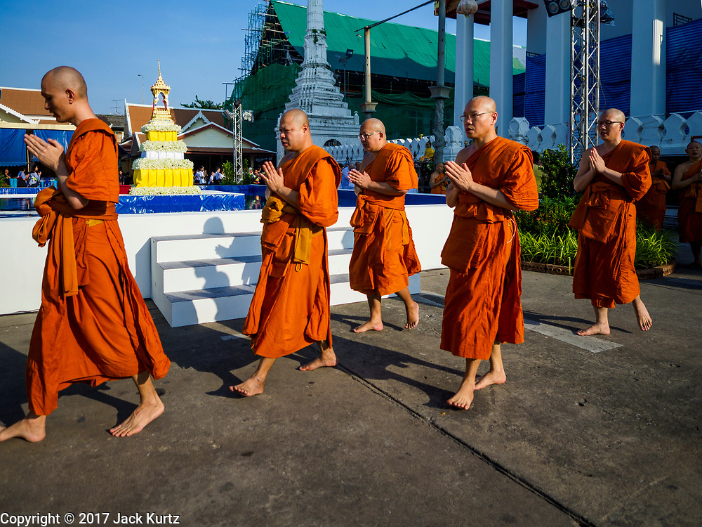 "03 NOVEMBER 2017 - BANGKOK, THAILAND: Buddhist monks participate in a procession at the beginning of Loi Krathong at Wat Prayurawongsawat on the Thonburi side of the Chao Phraya River. Loi Krathong is translated as ""to float (Loi) a basket (Krathong)"", and comes from the tradition of making krathong or buoyant, decorated baskets, which are then floated on a river to make merit. On the night of the full moon of the 12th lunar month (usually November), Thais launch their krathong on a river, canal or a pond, making a wish as they do so. Loi Krathong is also celebrated in other Theravada Buddhist countries like Myanmar, where it is called the Tazaungdaing Festival, and Cambodia, where it is called Bon Om Tuk.     PHOTO BY JACK KURTZ"