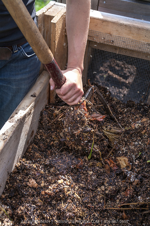 A gardener turns and aerates compost in a wooden bin with a garden fork.