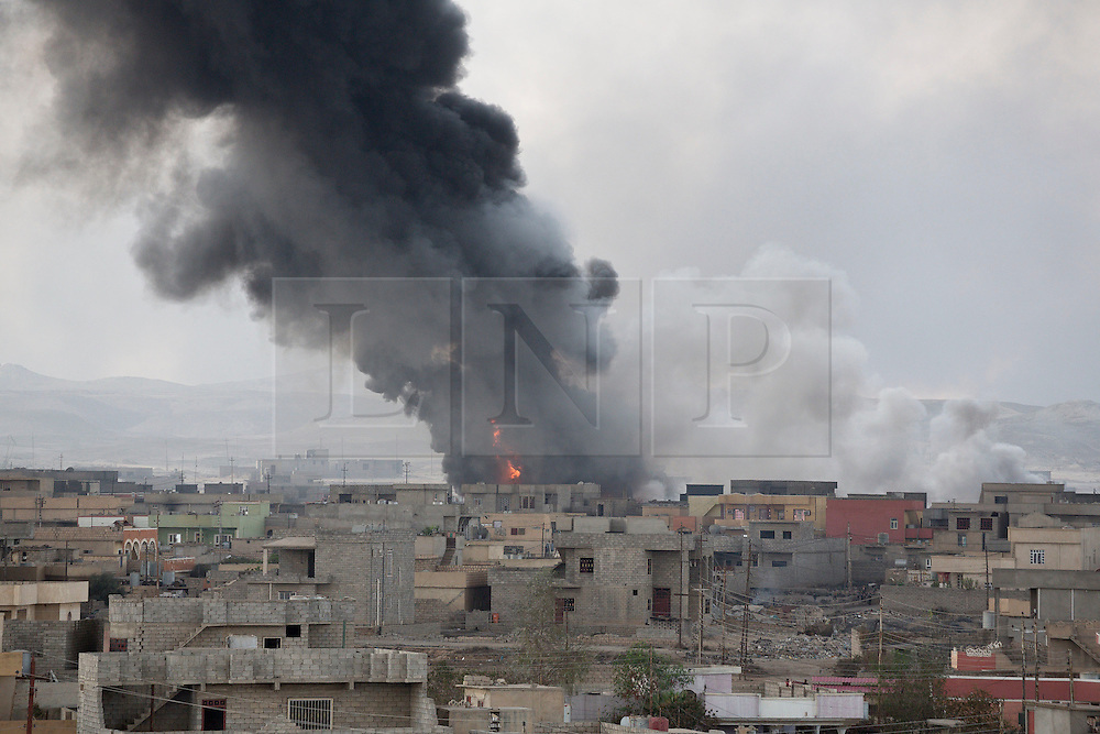 Licensed to London News Pictures. 02/11/2016. Qayyarah, Iraq. Smoke and flames rise from a burning oil well, set alight by retreating Islamic State militants, located with the Iraqi town of Qayyarah.<br /> <br /> Two months after being liberated from the Islamic State, the Iraqi town of Qayyarah, located around 30km south of Mosul, is still dealing with the environmental repercussions of their ISIS occupation. The town's estimated 15,000 inhabitants constantly live under, and in, heavy clouds of smoke which often envelope the settlement. The clouds emanate from burning oil wells in a nearby oil field that were set alight by retreating ISIS extremists after a two year occupation. The proximity of the fires, often right next to homes within the town, covers many buildings and residents with thick soot and will lead to long term health and environmental implications. Photo credit: Matt Cetti-Roberts/LNP