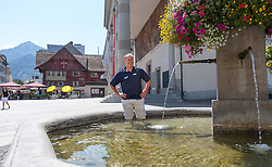 20.08.2012, Stadtbrunnen am Marktplatz, Dornbirn, AUT, EBEL, Dornbirner Eishockey Club, DEC Media Days 2012, im Bild Dave MacQueen, (Dornbirner Eishockey Club, Head Coach) nimmt eine Abkühlung im Stadtbrunnen von Dorbirn, im Hintergrund das Wahrzeichen von Dornbirn das rote Haus // during the DEC Media Days 2012 of Erste Bank Icehockey League Team, Dornbirner Icehockey club at the City, Dornbirn, Austria, 2012/08/20, EXPA Pictures © 2012, PhotoCredit: EXPA/ Peter Rinderer