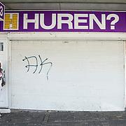 Nederland Rotterdam 2 april 2009 20090405 Foto: David Rozing ...Allochtone vrouw staat naast gesloten winkelpand, groot reclamebord met tekst huren? boven de afgesloten etalage. bedrijfruimte te huur, leegstand, leegstaand, ..Foto: David Rozing