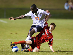 St. John's Red Storm midfielder Kyle Hoffer (8) slide tackles Virginia Cavaliers midfielder Tony Tchani (23).  The Virginia Cavaliers fell to the St. John's Red Storm 1-0  in NCAA men's soccer at Klockner Stadium on the Grounds of the University of Virginia in Charlottesville, VA on August 29, 2008.