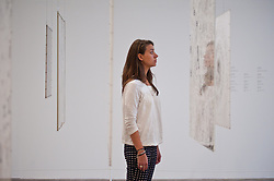 "Mira Schendel at Tate Modern in London. <br /> Tate Modern employee poses next to works entitled ""Graphic Object"" by Mira Schendel, Tate Modern, London, Tuesday, 24th September 2013. Picture by Piero Cruciatti / i-Images"