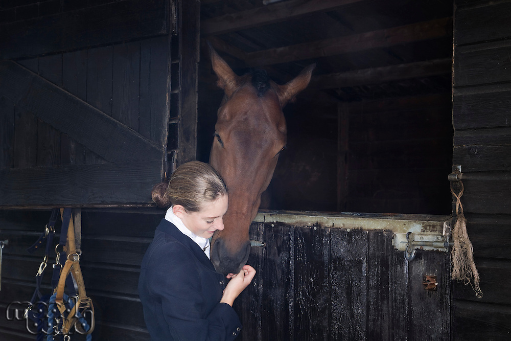 Female horseback rider with horse in stable