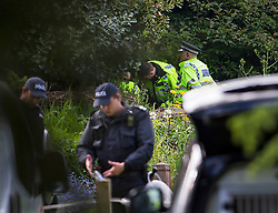 © London News Pictures. 24/05/2015. London, UK. Police officers in riot gear searching through bushes at Oxford University Parks in Oxford City centre, where police are currently searching for 21 year old Jed Allen who is wanted in connection with the deaths of a man, a woman and a girl, found at a property in Didcot,  Oxfordshire.. Photo credit: Ben Cawthra/LNP