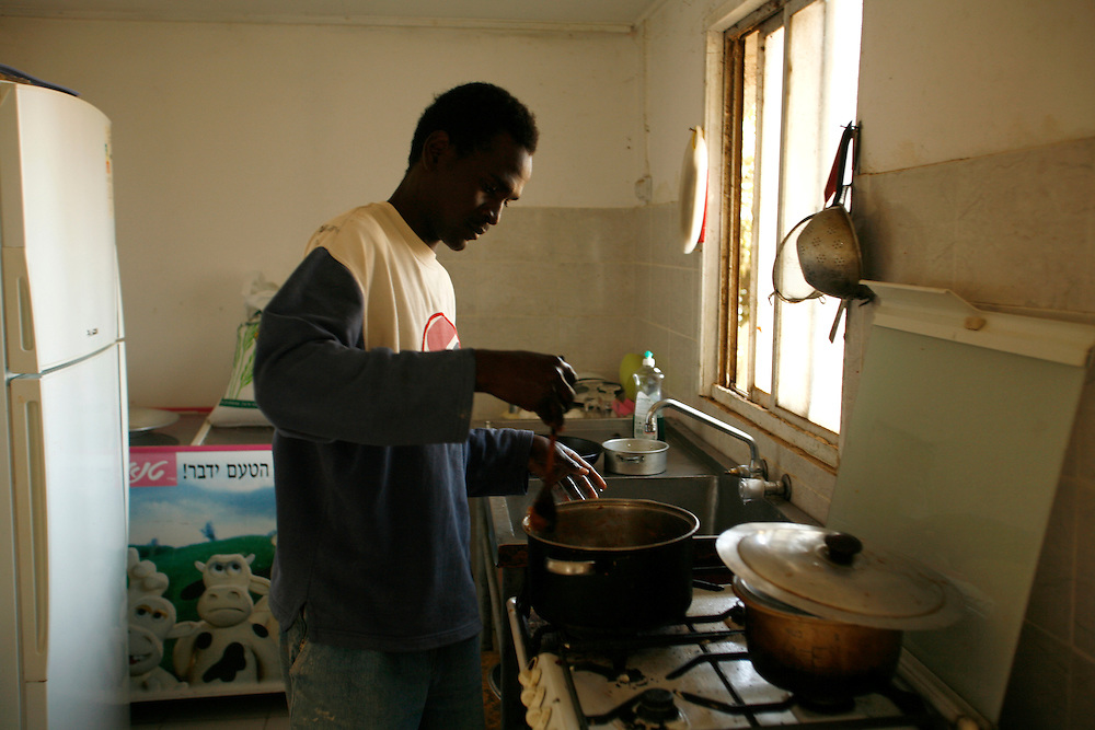 Isadin Ahmed Ibraham   25 cooking lunch at his kitchen in Kibbutzz Urim, Israel at Wednesday November 14.2007.... Isadin born in Darfur and run away from Darfur after his village was burnt down and most of the people were dead... He run away to Khartoum and from there to Egypt, in Egypt he didn?t got a refugee papers from the UN. He say it hard to be in Egypt with no papers so he keep his journey to Israel crossing the Sinai desert, wean he pass illegally the border to Israel, the Israeli army got him and put him in detention camp and then he  got to Kibbutz Urim a year and three month ago, Kibbutz Urim voluntary to adopt refugees from Darfur and give them work place to stay and all they needs ..Today one of the family?s in the Kibbutz are taking care of him and he work in irrigation for 10 -12 hours a day with Israeli kibbutz member named Oz Gang ...Mohammad say he is happy in Israel and I have food place to sleep and food and no one is stopping him from travel in Israel, but he still didn?t get refugee status from the UN. And because of that he is not filling free.....