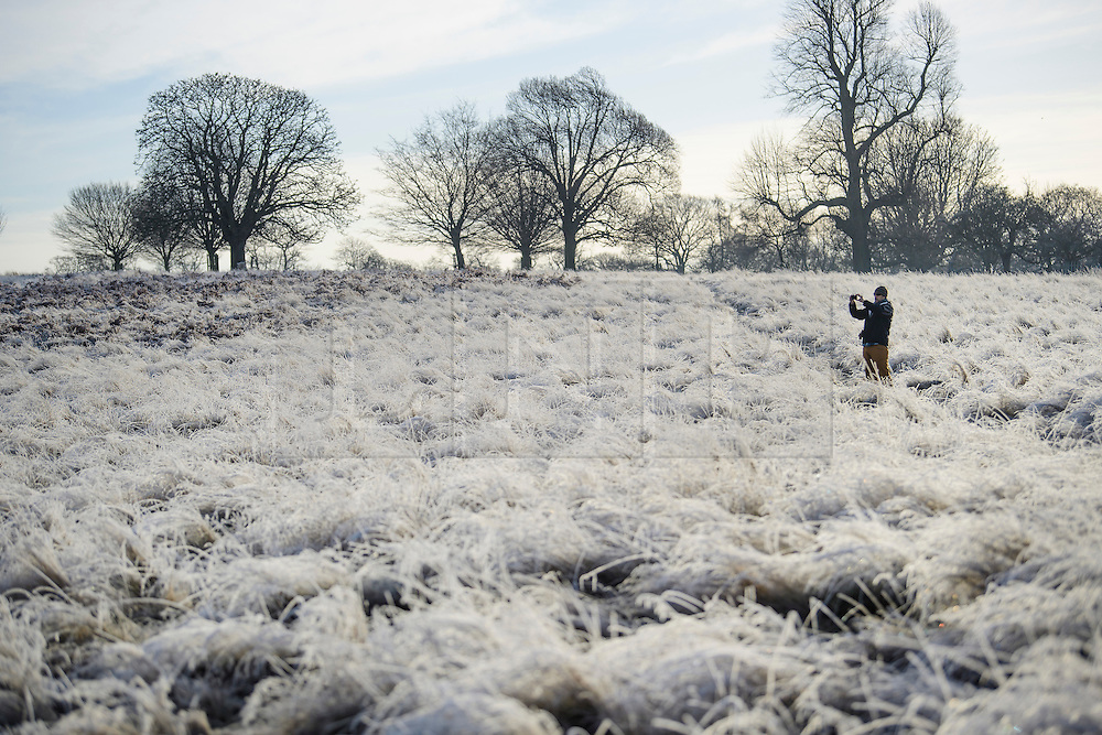 © Licensed to London News Pictures. 03/01/2017. London, UK. A man takes a picture of a frost covered landscape in Richmond Park in London as temperatures in the capital drop below zero. . Photo credit: Ben Cawthra/LNP