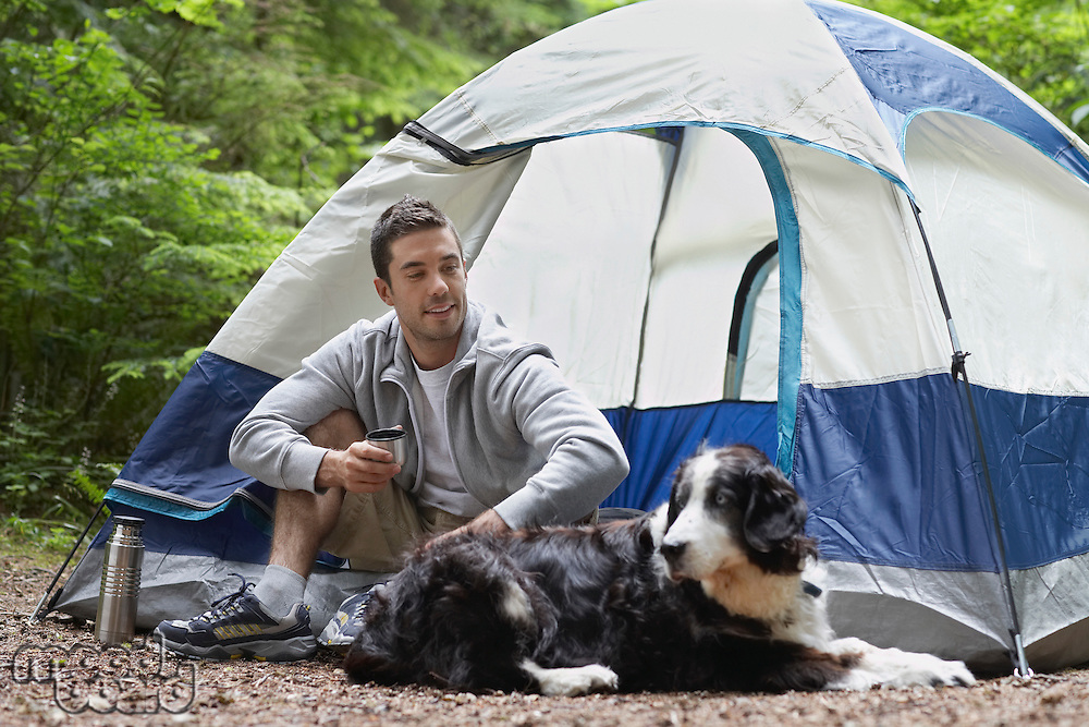Man with dog sitting by tent