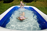 Haylee Crum, 9, swims away from her sister, Mackee Crum, 7, as they play in their inflatable pool Monday behind their apartment in Post Falls. During the city council meeting tonight, Post Falls officials will vote on proposed water and sewer rate increases.