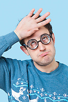 Geek young man wearing novelty glasses with hand on head over blue background