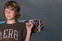 Teenage boy (13-15) holding skateboard standing against sky portrait