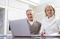 Middle-aged couple working on laptop in kitchen