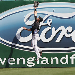 March 12, 2011; Fort Myers, FL, USA; The ball punches a hole in a sign as it hits the wall as Florida Marlins right fielder Josh Kroeger (63) jumps in an attempt to make a play on the ball during a spring training exhibition game against the Boston Red Sox at City of Palms Park. The Red Sox defeated the Marlins 9-2.  Mandatory Credit: Derick E. Hingle