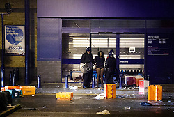 © Licensed to London News Pictures. 08/08/2011 LONDON, UK. Police officers detail a suspected looter, wearing a Currys' staff fleece, after she was caught inside the Brixton Branch of the UK electrical chain. The looting took place after a second night of violence hit several parts London. Photo credit: Matt Cetti-Roberts/LNP