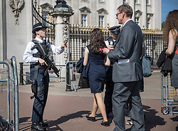 © Licensed to London News Pictures. 24/05/2017. London, UK. An armed police woman checks passes for people entering Buckingham Palace for a garden party - security in the capital has been stepped up after the Manchester Arena bombing. The terrorism threat level has been raised to critical and Operation Temperer has been deployed. 5,000 troops are taking over patrol duties under police command. Photo credit: Peter Macdiarmid/LNP