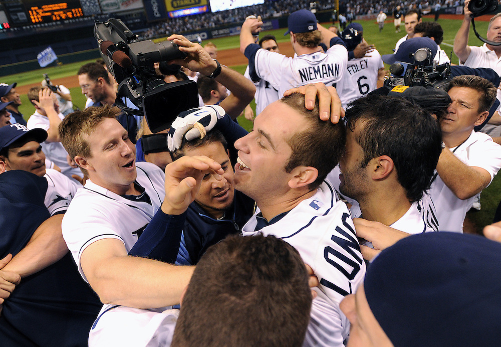 Tampa Bay Rays' Evan Longoria is swamped by teammates at the plate after Longoria hit a walk-off homerun giving the Rays an 8-7 win over the Yankees and American League Wildcard spot Wednesday, Sept. 28, 2011 in St. Petersburg.