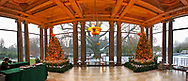At Westbury House, two Christmas trees flank the Porch facing West, with panoramic view of snowy grounds during Winter Holiday event at Old Westbury Gardens.