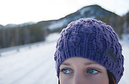 A woman wears a purple woollen hat in winter conditions whilst walking in the frozen canadian countryside