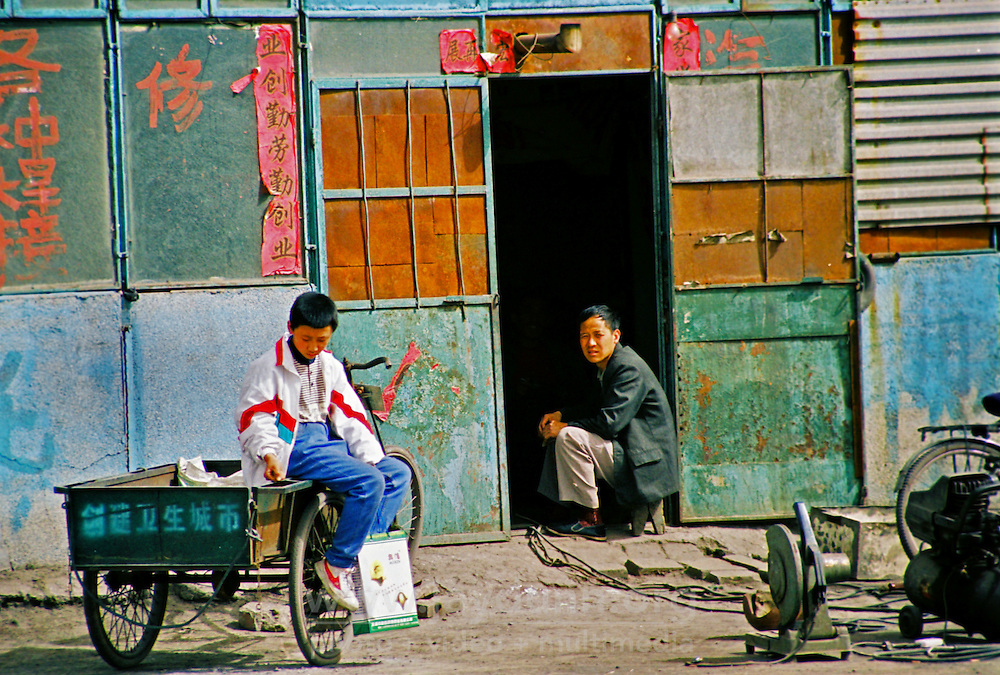 China, Taiyuan, 2007. Machines idle for now, a metalworker takes in the view from his roadside shop near the outskirts of Taiyuan..