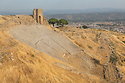 Hellenistic Theatre, built 2nd century BC under the reign of Attala II, Pergamon, with view of the modern-day city of Bergama in the distance, Izmir, Turkey. The theatre seated 10,000 people and would have had a wooden stage which was erected for each performance. It is the steepest theatre of the ancient world and has 78 rows of seats in 3 horizontal sections. The seats are of andesite and trachyte, except for the marble seat of honour above the first diazoma. Picture by Manuel Cohen