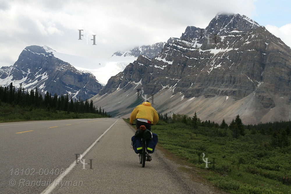Touring cyclist pedals along Icefields Parkway near Bow Mountain in Banff National Park; Alberta, Canada.