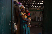A Sidi mother holds her child inside her home in the small town of Bedi.