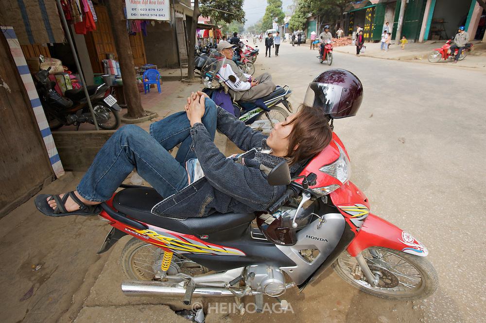 Tam Duong market. Man having a nap on his motorbike.