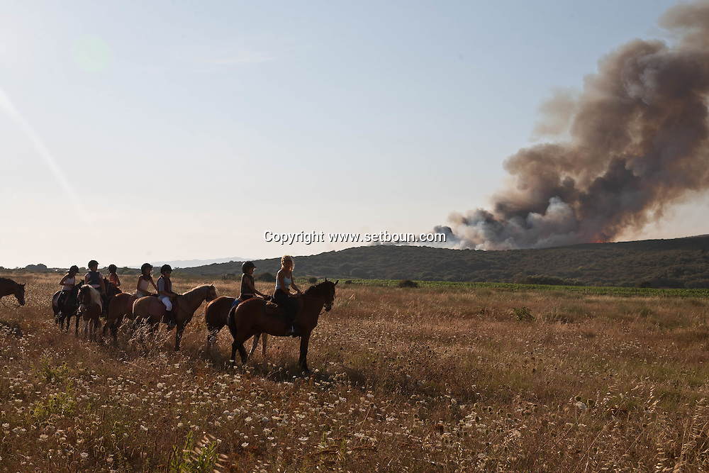 des jeunes a cheval, canadair survolant un incendie, les touristes en vacances regardent.   Corse du sud .  Propriano   /  CORS002