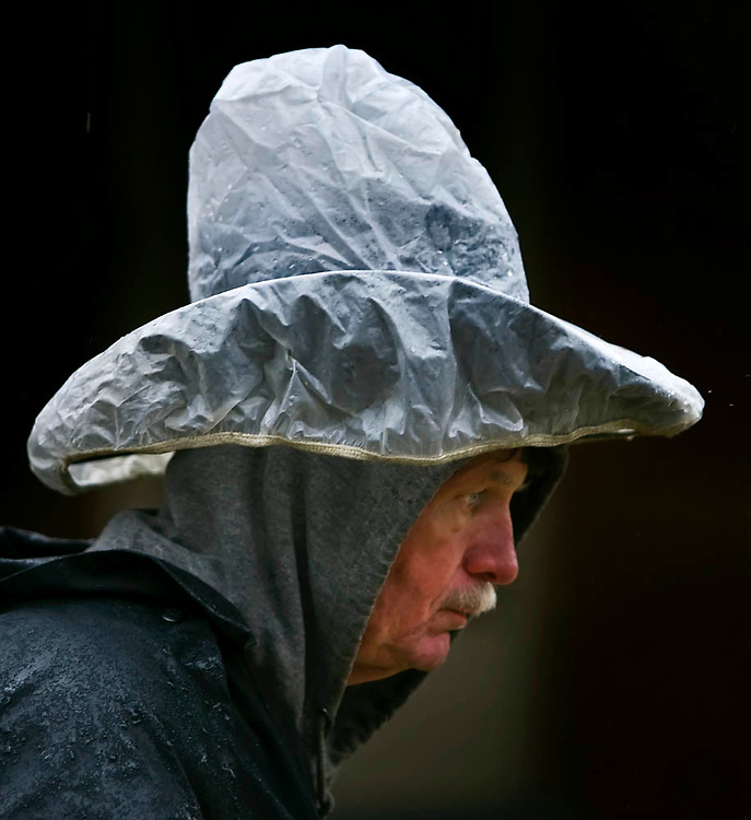 "Mike Prince of Kansas City knew his priorities on a soggy Sunday afternoon on a walk at 38th and Bell...to keep his cowboy hat dry. ""If you spend $100 to $200 (on a hat)....you don't want to screw that up,"" Prince said about his plastic covering."
