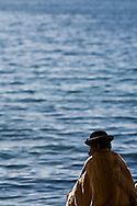 A loyal Aymara Indian woman waits for a boat next to Lake Titicaca, Bolivia.