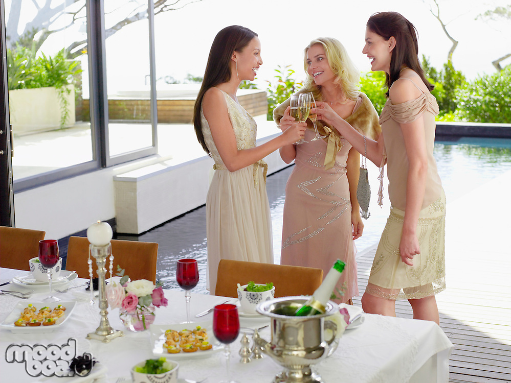 Young female Friends drinking and socialising near pool at Dinner Party