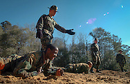 Drill Instructor Staff Sgt. Kenneth Adams points the way while encouraging soldiers from Charlie Company 2nd Battalion, 58th Infantry Regiment of the Infantry Training Brigade at Ft. Benning as they low crawled in the sand on the  ITB Obstacle Course. (Alan Lessig/Army Times)