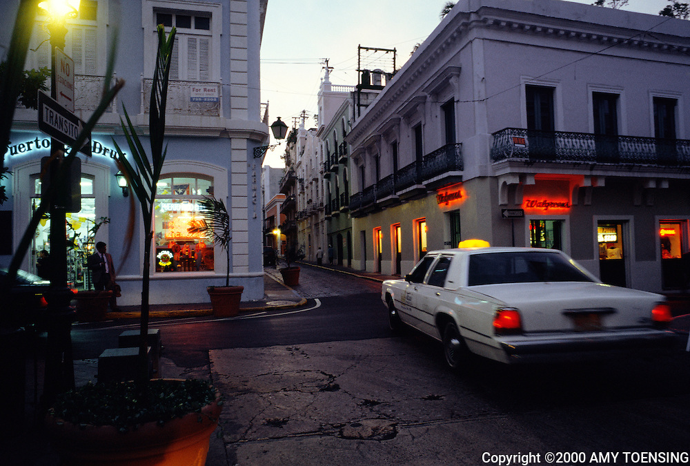 OLD SAN JUAN, PR - JULY 23: A taxi drives past the main square July 23, 2002 in Old San Juan, Puerto Rico. Puerto Rico was an outpost of Spanish colonialism for 400 years, until the United States took possession in 1898. Today Puerto Rico's Spanish-speaking culture reflects its history - a mix of African slaves, Spanish settlers, and Taino Indians. Puerto Ricans fight in the U.S. armed forces but are not entitled to vote in presidential elections. They passionately debate their relationship with the U.S. with about half the island wanting to become the 51st state and the other half wanting to remain a U.S. commonwealth. A small percentage feel the island should be an independent country. While locals grapple with the evils of a burgeoning drug trade and unchecked development, drumbeats still drive the rhythms of African-inspired bomba music. (Photo By Amy Toensing) _________________________________<br /> <br /> For stock or print inquires, please email us at studio@moyer-toensing.com.